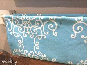 DIY bookshelves using dowel rods and fabric.
