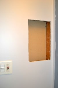 Control bathroom countertop clutter by building a storage shelf in your wall, between the studs | how to build a shelf in your wall