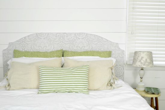 vintage farmhouse master bedroom wit stenciled headboard