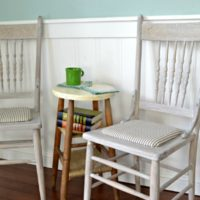 Refinished farmhouse chairs with a whitewash finish and mattress ticking seat