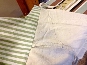 I love how the lining of this pillow cover hides the pillow inside! With this tutorial, it's easy and inexpensive to sew a farmhouse pillow out of a drop cloth.
