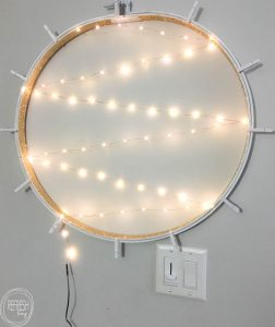 What a smart idea! Use an old embroidery hoop to create a DIY Christmas card holder, complete with copper wire LED lights.