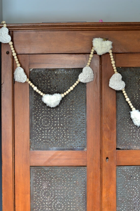 Such an easy DIY project to decorate for Valentine's Day. You could easily change the colors as well, but I like the farmhouse look of the white yarn and wooden beads.