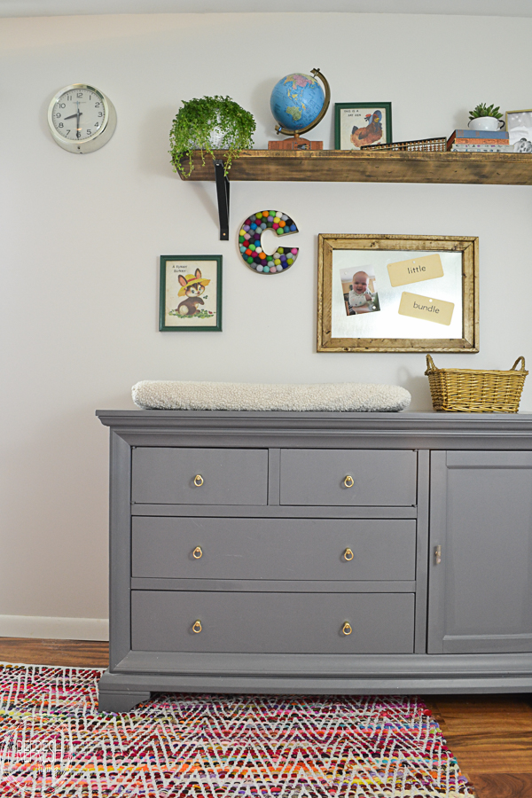 What a fun way to decorate a nursery! This gallery wall with a large shelf is perfect for displaying vintage finds to give the room a vintage classroom feel.