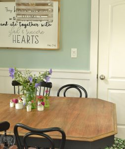 This dining room table only cost $37 at a thrift store! After stripping and bleaching the top and painting the base, it looks like a new piece of furniture! Refinished farmhouse table with natural wood top and painted gray base.