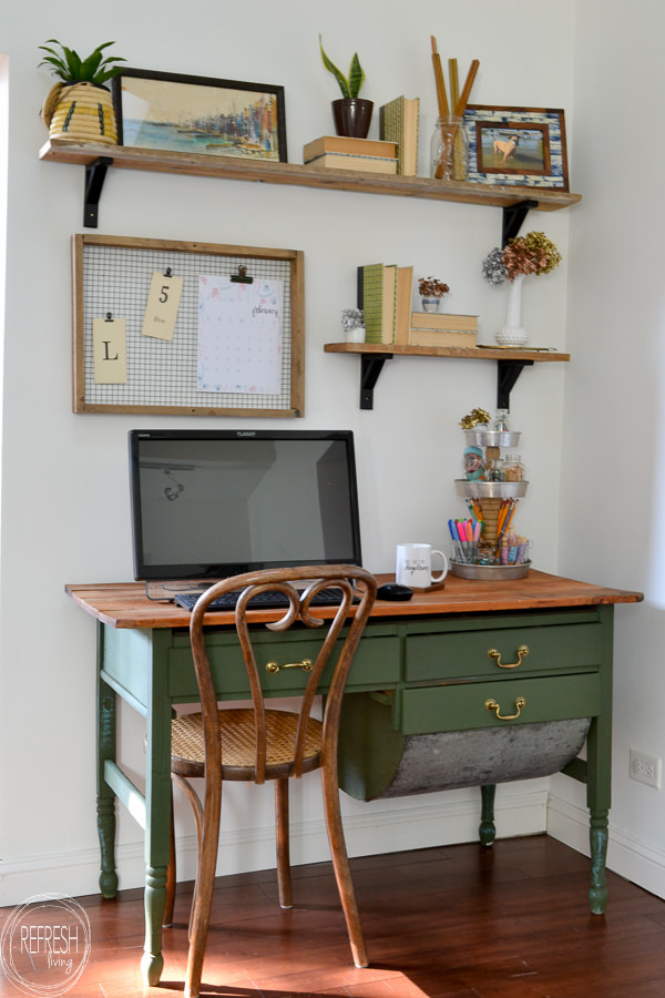An antique baker's table becomes a desk by removing one of the flour drawers. Vintage modern office with open shelves and farmhouse boho vintage feel. Dark green desk with natural wood top desk via Refresh Living.