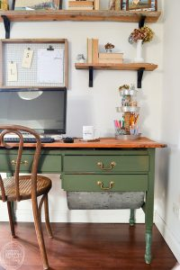 An antique baker's table becomes a desk by removing one of the flour drawers. Vintage modern office with natural wood. Dark green desk with natural wood top desk via Refresh Living.