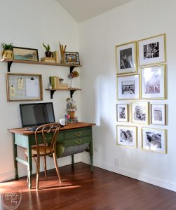 An antique baker's table becomes a desk by removing one of the flour drawers. Vintage modern office with open shelves and farmhouse boho vintage feel. Dark green desk with natural wood top desk.