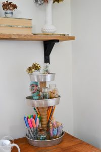 Great solution for office organization - a tiered tray with glass bottles holds craft and office supplies. Gives the space a vintage farmhouse feel.