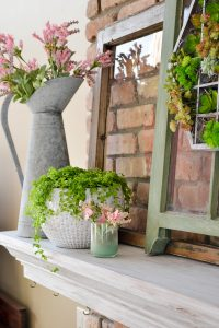 This spring decor has a vintage farmhouse feel. Mantel decorated for spring with green and pink, old windows, and succulents. Spring home tour with upcycled and vintage finds.