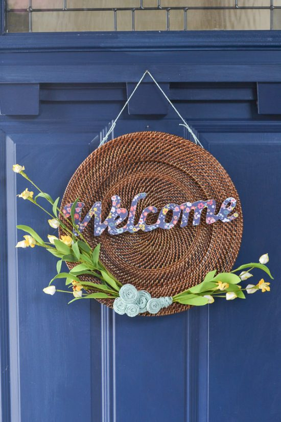 This is a plate charger - I see these at the thrift store all the time. Now, I'll definitely be picking one up to make a wreath like this one. DIY spring wreath with wood, twine, yellow flowers and welcome cut out.
