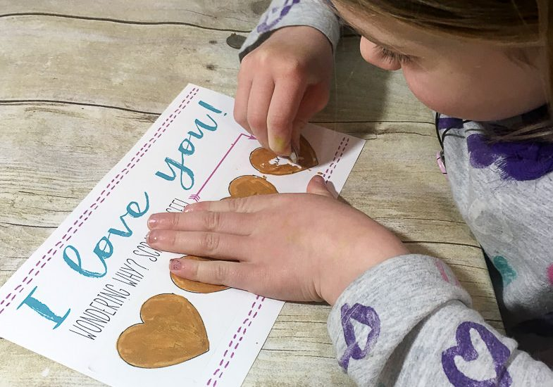 DIY Valentines for kids or grandkids with scratch off reasons I love you. Just print off the cards, write in the hearts, add tape, and paint the DIY scratch off paint onto the hearts. The scratch off paint can be made with stuff that I already have already the house.