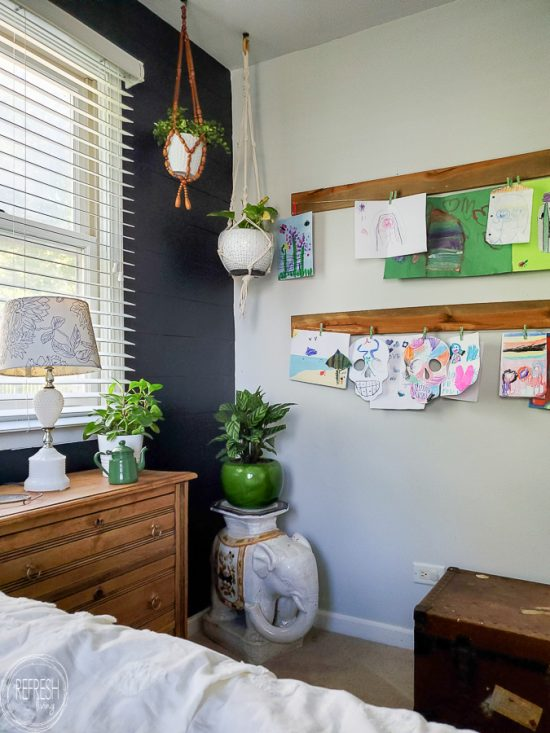 Check out this master bedroom makeover completed with refinished furniture, a DIY modern headboard, a painted black feature wall, vintage fabric and a kids art display.