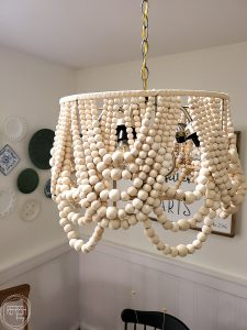 I saved hundreds of dollars by making this farmhouse light fixture! This DIY beaded chandelier was made from a $10 thrift light fixture, an old lampshade, and lots of beads.