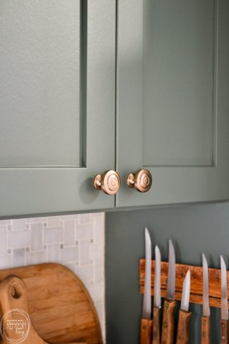 These champagne bronze knobs look perfect with green cabinets. It looks like a subtle brushed brass finish that is modern and goes well with any color.