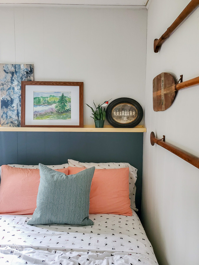 Create the look of a headboard with paint and a DIY wood shelf. It's easy and inexpensive to build the picture frame shelf too!