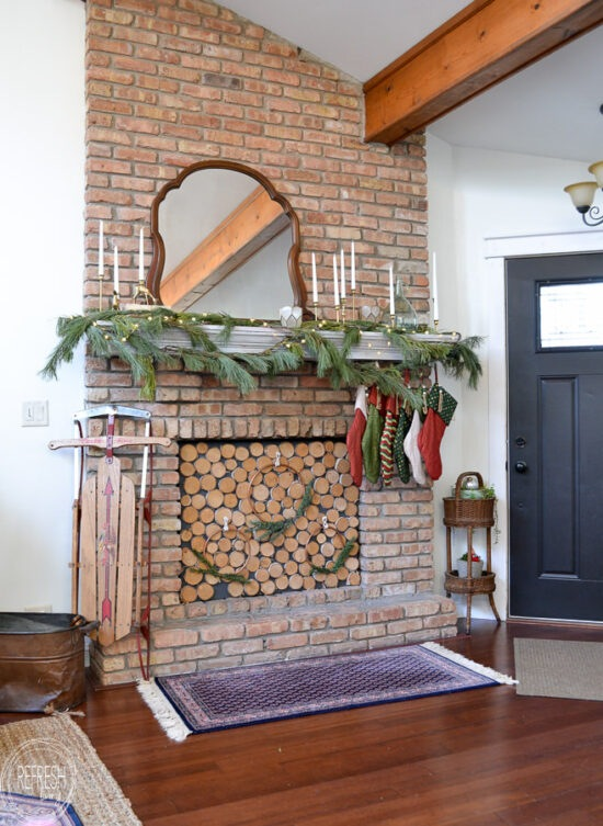 Mix of greenery, brass candlesticks, and vintage decor in this Christmas mantel