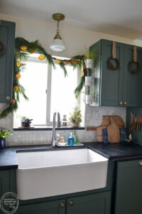 Natural wreaths and orange garland look perfect next to these green kitchen cabinets.