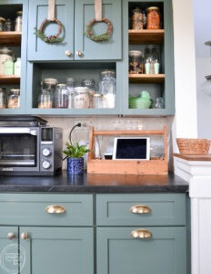 Natural wreaths on green kitchen cabinets are an easy DIY project with items from the craft store.