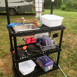 DIY camp kitchen made from plastic shelves and small sink and faucet