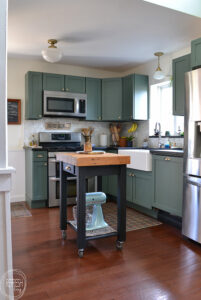 small kitchen island with butcher block top and black base in kitchen with green cabinets