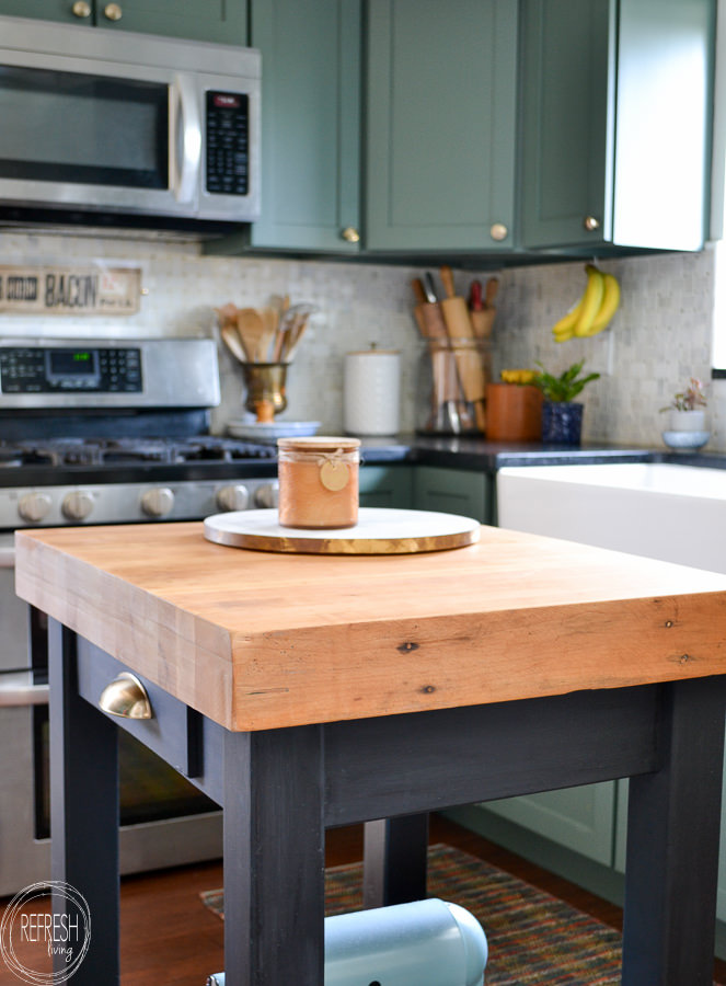 small kitchen island with butcher block top and black base