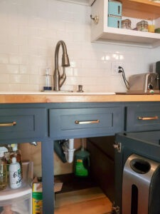 Kitchen with large bottle of dish soap under the cabinet with tube up to soap dispenser